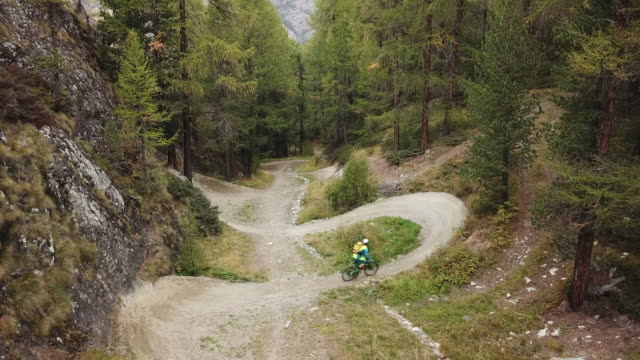 aerial view of mountain biker descending flow trail through forest - strada in terra battuta video stock e b–roll