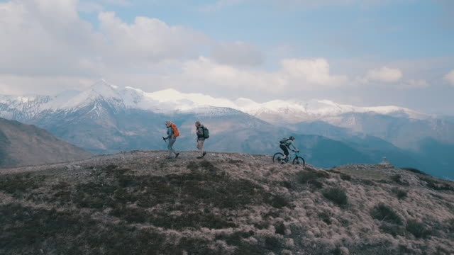 Aerial view of mountain biker descending ridge passes hikers ascending