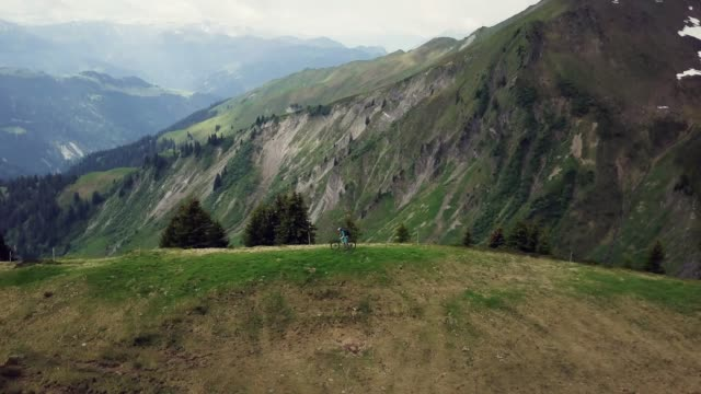 luftaufnahme der mountainbiker auf grasbewachsenen alpenkamm in alpen - mountainbiking stock-videos und b-roll-filmmaterial