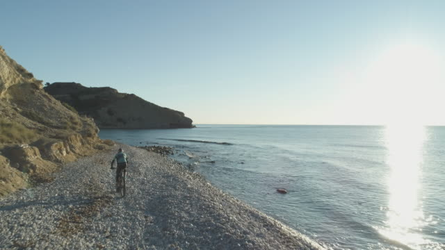 vidéos et rushes de aerial view of mountain biker rides along empty rocky beach - paysage marin