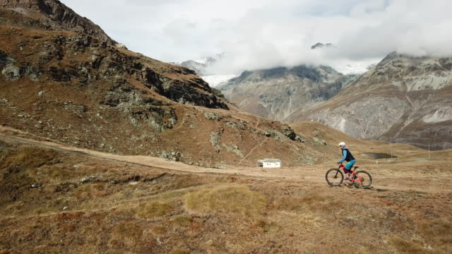 aerial view of mountain bikers ascending high alpine trail - サイクリングロード点の映像素材/bロール