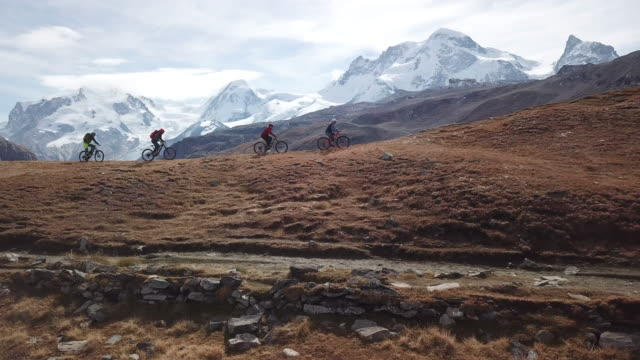 Aerial view of mountain bikers ascending high alpine trail, view of glacier