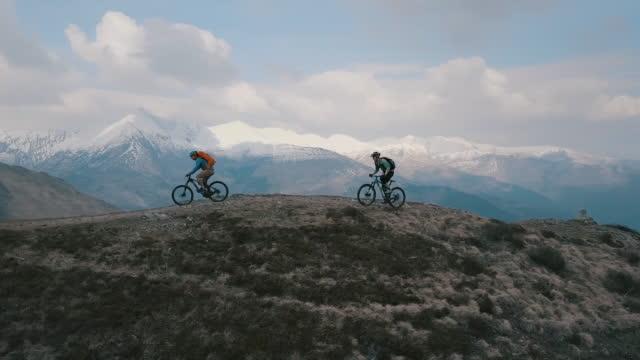 aerial view of mountain bikers ascending mountain ridge below snow capped mountains - mountain ridge stock videos & royalty-free footage