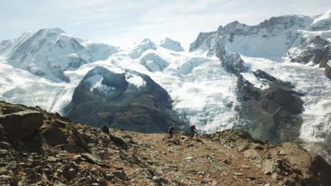 vidéos et rushes de aerial view of mountain bikers descending high alpine trail, view of glacier - faire du vélo tout terrain
