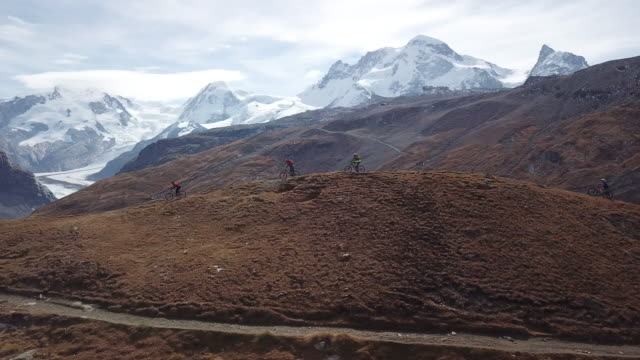 aerial view of mountain bikers descending high alpine trail, view of glacier - サイクリングロード点の映像素材/bロール