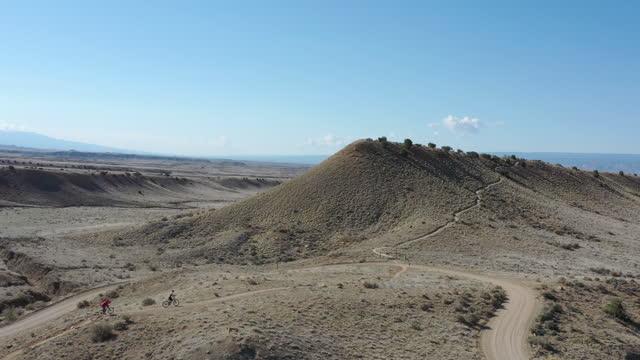vídeos y material grabado en eventos de stock de vista aérea de los ciclistas de montaña siguiendo el camino del desierto - menos de diez segundos