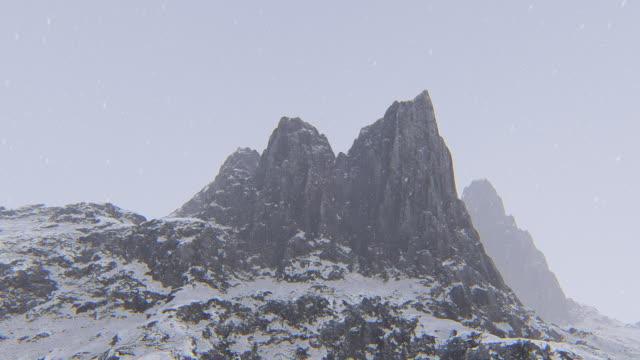 vídeos de stock, filmes e b-roll de vista aérea do pico de montanha com neve - coberto de neve