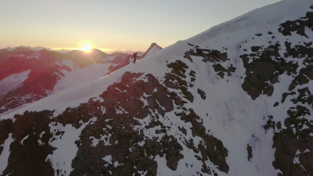 Aerial view of mountaineers reaching summit of mountain at sunrise