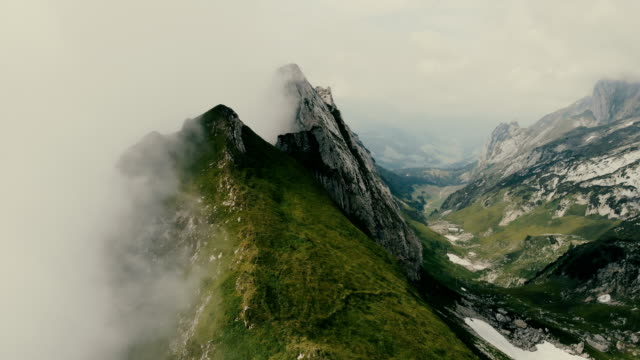 vídeos de stock e filmes b-roll de aerial view of mountains in fog  switzerland - horizontal