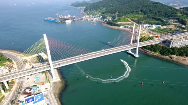 aerial view of moving tourboat under geobukseondaegyo brige and overhead cable car on the sea with landscape of yeosu - tourboat stock videos & royalty-free footage
