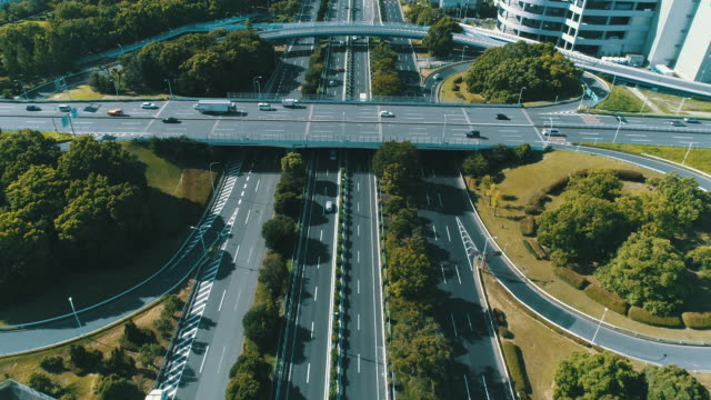 aerial view of multiple lane highway with modern cityscape - straßenüberführung stock-videos und b-roll-filmmaterial