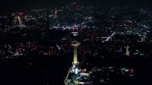 ソウルのダウンタウンのスカイラインにあるnソウルタワーの空中写真で、韓国のソウル市で夜に南山山のライトトレイルを楽しめます。 - 朝鮮半島点の映像素材/bロール