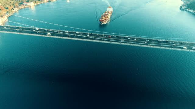 ボスポラス海峡の橋の下を横断する航海船の航空写真 - 日の出時のイスタンブールボスポラス海峡のファティ・スルタン・メフメット橋のドローンショット - nautical vessel点の映像素材/bロール