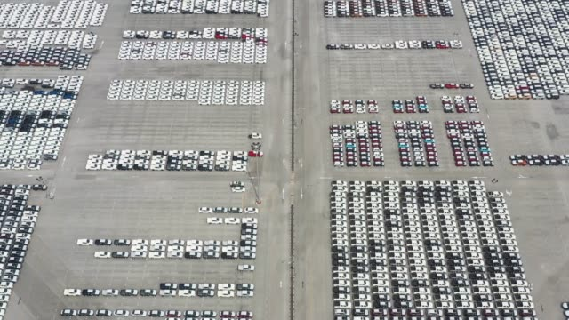 aerial view of new cars at the parking area of automobile factory.export and import transportation vehicle - reduction stock videos & royalty-free footage
