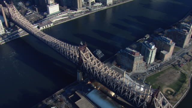 aerial view of new york city's queensboro bridge, also known as the 59th street bridge. the cantilever bridge crosses the east river and roosevelt island to connect manhattan and queens. - cantilever bridge stock videos & royalty-free footage