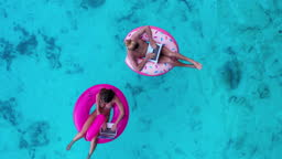 Aerial view of nice day,Young couple working by computer during social distancing using laptop computer and video conferencing technology on rubber ring in the sea.World at work drone view concept.