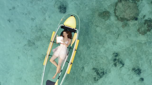 aerial view of nice day,young women age 25 yearold laying down reading a book in a boat on sea.tropical vacation activities concept. - kayaking stock videos & royalty-free footage