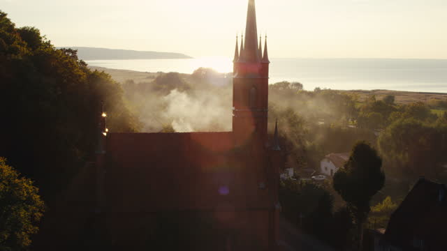 aerial view of nicolaus copernicus museum silhouette. sun setting above coast in frombork - castle stock videos & royalty-free footage