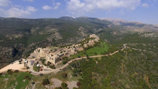 vidéos et rushes de aerial view of nimrod fortress  (qal'at namrud) with hermon mountain covered with snow in background - byzantin
