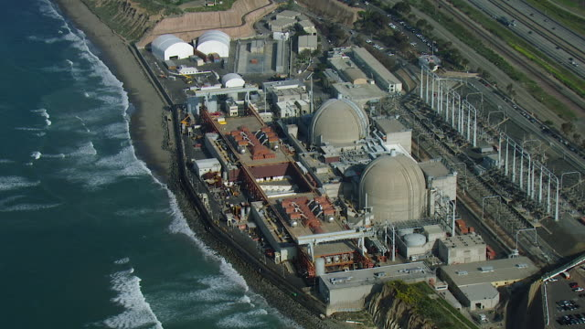 vídeos de stock e filmes b-roll de aerial view of nuclear generating station on coast - central de energia nuclear