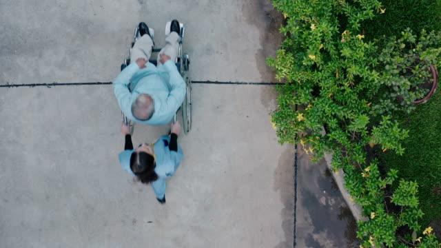 自宅で先輩と車椅子を押す看護師の空中写真。 - 福祉点の映像素材/bロール