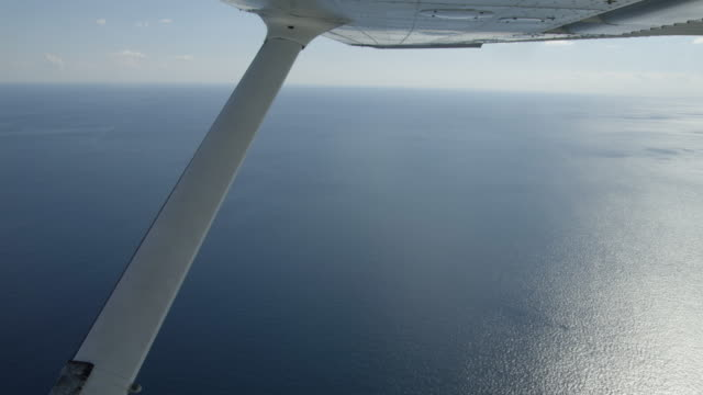 WS aerial view of ocean and  airplane wing seen out of window of light Cessna aircraft