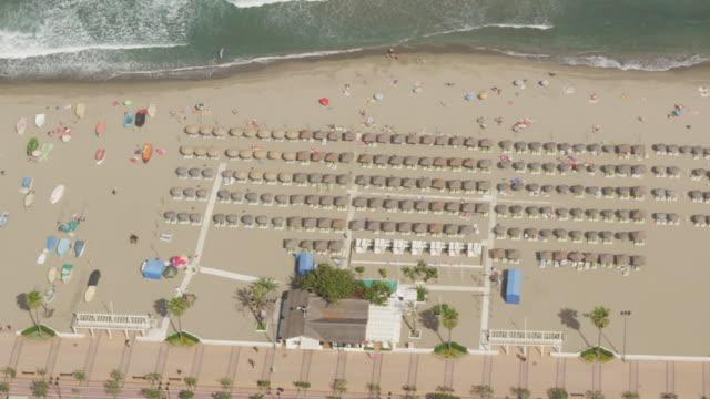 stockvideo's en b-roll-footage met aerial view of ocean beach with boats, umbrellas and bathers - zonwering