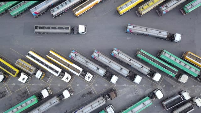 aerial view of oil trucks are parked in the parking lot waiting to transport the oil. - automobile industry video stock e b–roll