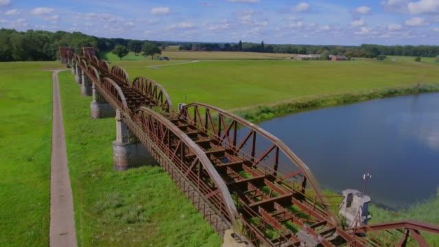 vídeos de stock, filmes e b-roll de vista aérea da velha ponte elbbrücke doemitz no rio elba - alemanha - rio elbe
