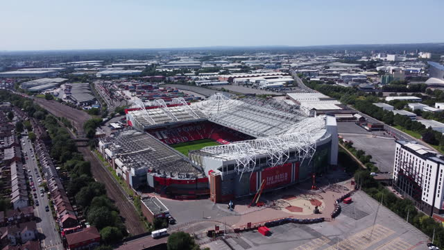 aerial view of old trafford football stadium. rising and racking-in. - image stock videos & royalty-free footage
