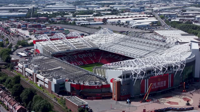 aerial view of old trafford football stadium. tracking-in. - real time stock videos & royalty-free footage