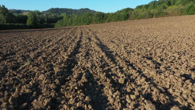 vídeos de stock e filmes b-roll de aerial view of on a plowed field - terra cultivada