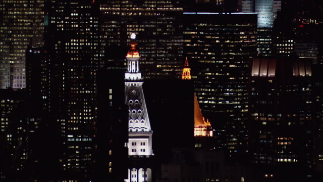 Aerial view of ornate illuminated rooftops in New York City at night.