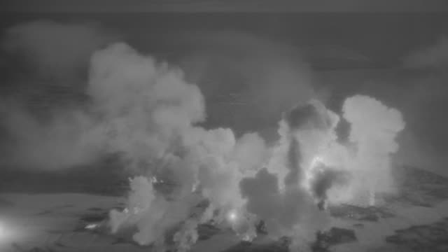 stockvideo's en b-roll-footage met ws aerial view of over area being bombed from above explosions going off as planes fly through smoke filling sky - luchtaanval