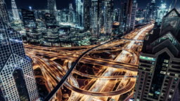 T/L Aerial View of Overpass, Metro and City Traffic at Night / Dubai, UAE