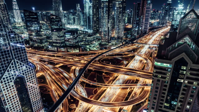t/l aerial view of overpass, metro and city traffic at night / dubai, uae - elevated road stock videos & royalty-free footage