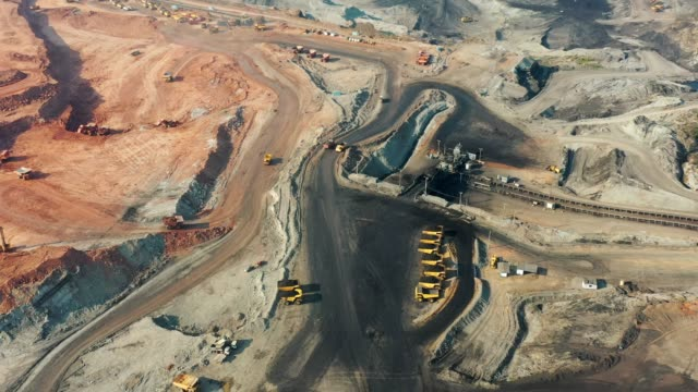 vídeos y material grabado en eventos de stock de vista aérea de parte de un pozo con gran camión minero trabajando, cargando bulldozer en cantera al aire libre - mina