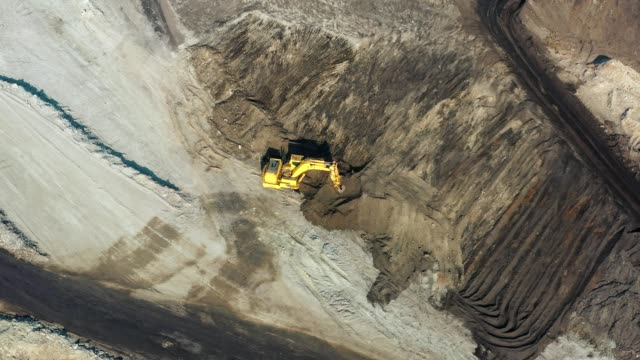 aerial view of part of a pit with big mining truck working, loading bulldozer in open air quarry - miniera video stock e b–roll