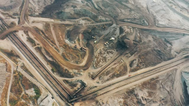 aerial view of part of a pit with big mining truck working, loading bulldozer in open air quarry - mining stock videos & royalty-free footage