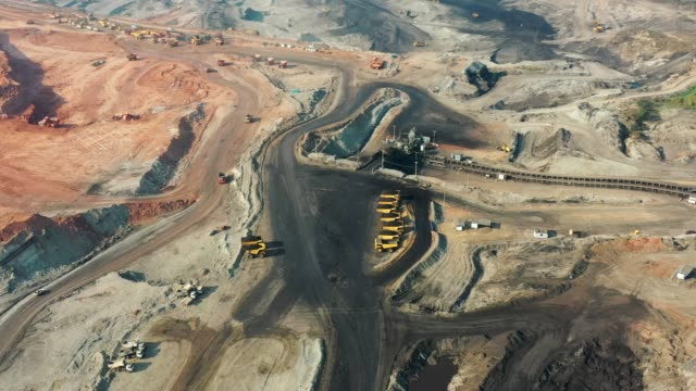 aerial view of part of a pit with big mining truck working, loading bulldozer in open air quarry - quarry stock videos and b-roll footage