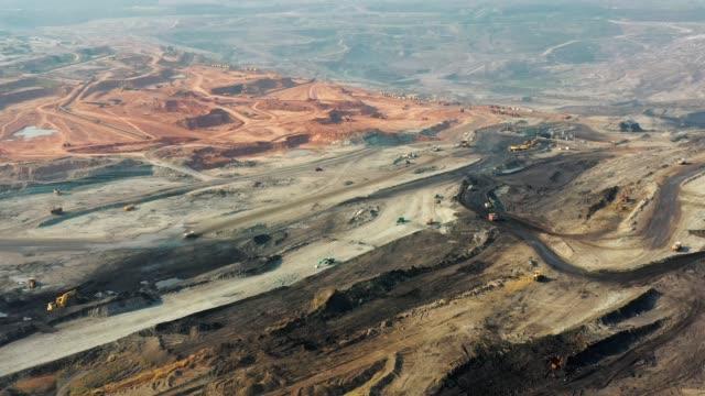 stockvideo's en b-roll-footage met luchtfoto van een deel van een put met grote mijnbouw truck werken, het laden van bulldozer in openlucht steengroeve - digging