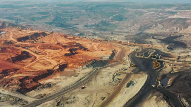 aerial view of part of a pit with big mining truck working, loading bulldozer in open air quarry - quarry stock videos & royalty-free footage