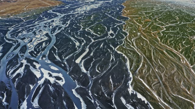 Aerial view of pattern flowing waters at delta in Iceland at winter