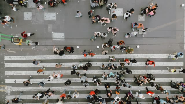 vídeos de stock e filmes b-roll de aerial view of pedestrians walking across with crowded traffic. - caminhada