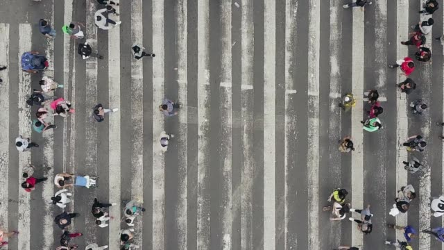 vídeos de stock e filmes b-roll de aerial view of pedestrians walking across with crowded traffic - marca de estrada