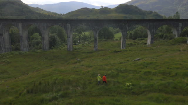 aerial view of people by glenfinnan railway viaduct - schottisches hochland stock-videos und b-roll-filmmaterial