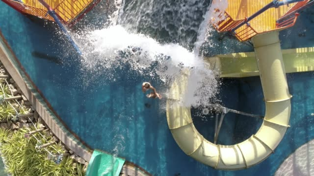 aerial view of people enjoying the water rides at a water park - acquascivolo video stock e b–roll