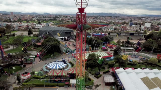 stockvideo's en b-roll-footage met luchtfoto van mensen plezier op een schommel rijden bij een pretpark - attractiepark