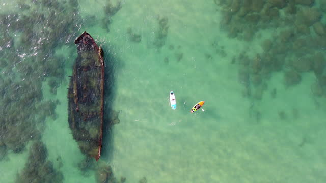 aerial view of people paddle boarding by shipwreck in sea, tourists enjoying vacation - arsuf, israel - water sport stock videos & royalty-free footage