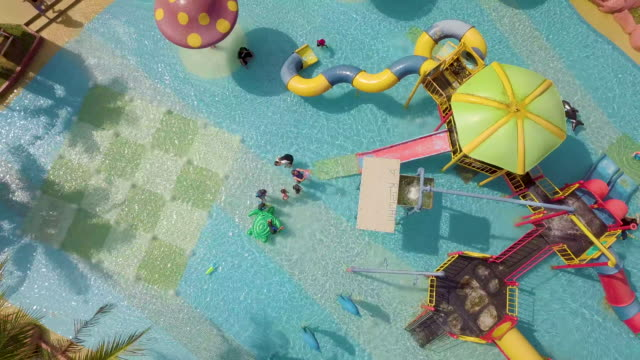 stockvideo's en b-roll-footage met aerial view of  people playing at swimming pool with water slides - glijbaan speeltuintoestellen